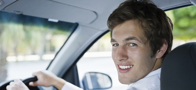 Portrait of a smiling young businessman driving car