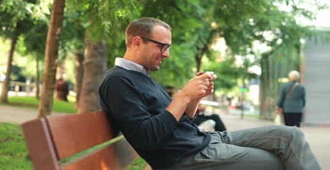 stock-footage-successful-young-man-playing-on-smartphone-in-the-city