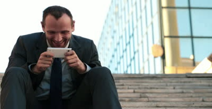 stock-footage-happy-businessman-playing-game-on-smartphone-in-the-city