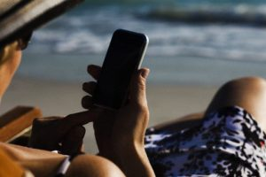 Woman text messaging with smartphone at beach --- Image by © Frederic Cirou/ès Photography/Corbis